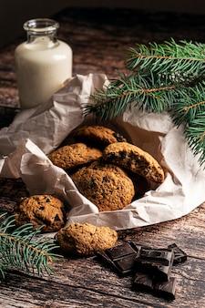 Домашнее печенье с шоколадной крошкой и молоком на темном деревянном фоне