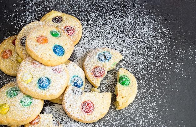 Шоколадная стружка и разноцветные конфеты домашнее песочное печенье обледенение на сером фоне. выборочный фокус.