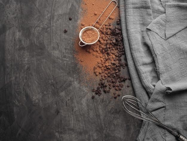 Шоколадная крошка, какао-порошок, венчик для теста лежит на сером фоне серой тканью. скопируйте пространство. вид сверху.