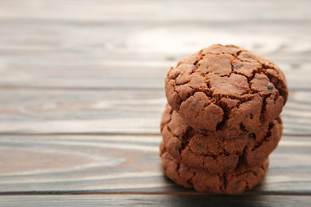 Chocolate chips cookies on brown wooden background.