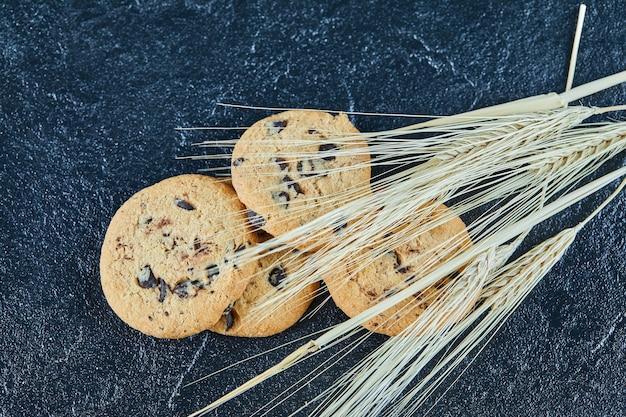 小麦の耳が付いている大理石の表面のチョコレートチップクッキー
