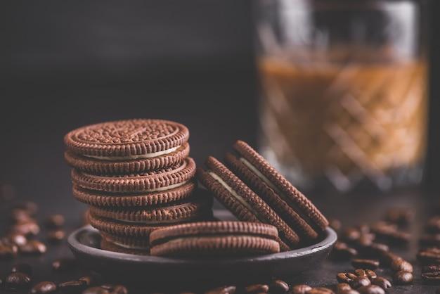 검은 배경에 초콜릿 칩 쿠키입니다. 배경에 라떼 커피입니다. 매트 톤.