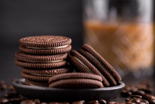 검은 배경에 초콜릿 칩 쿠키입니다. 배경에 라떼 커피입니다.