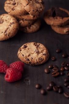 暗い古い木製のテーブルに赤いラズベリーとコーヒー豆とチョコレートチップクッキー。オーブンから出たばかり。