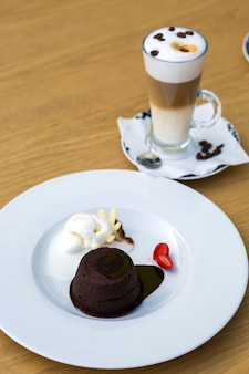 Chocolate chips served with ice cream and strawberry and three layered latte