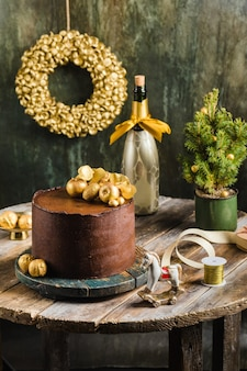 Chocolate christmas cake with gold decor champagne behind rustic style high quality photo