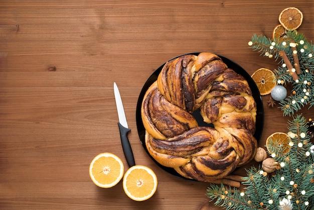 プレートにオレンジ色のシロップを細かく切った花輪の形をしたチョコレートのクリスマスの祖母。木製のテーブルの上のクリスマスの装飾。