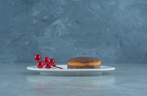 大理石の背景の大皿にチョコレートでコーティングされたケーキとクリスマスベリーのクラスター。高品質の写真