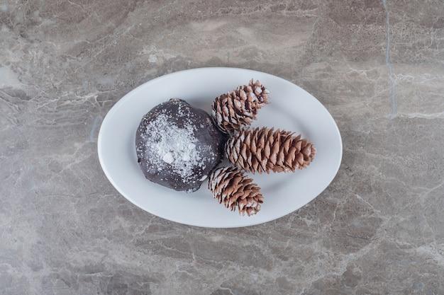 Торт в шоколаде и три сосновых шишки на блюде на мраморной поверхностиc