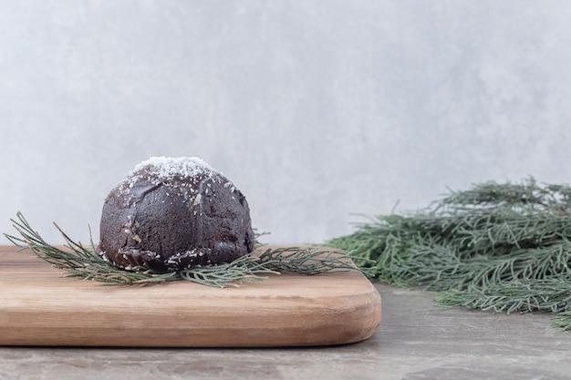 Torta ricoperta di cioccolato, tavola di legno e rami di pino su superficie di marmo