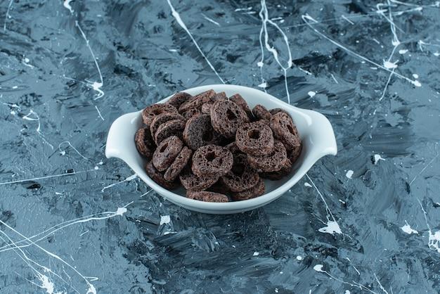 大理石の背景に、ボウルにチョコレートでコーティングされたコーンリング。