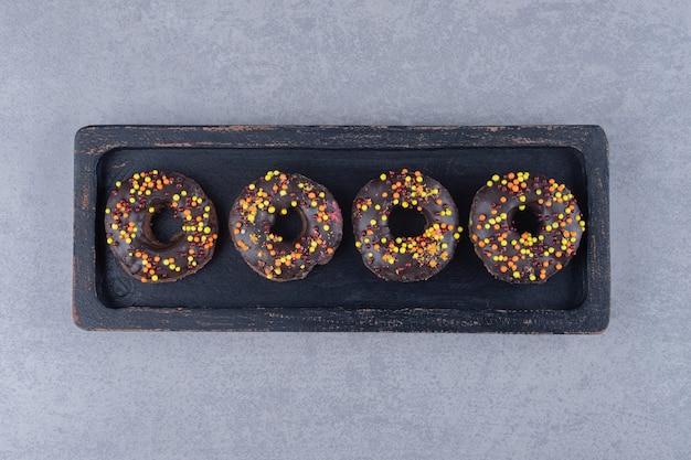 대리석 표면에 플래터에 초콜릿 코팅 된 도넛