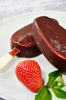 Chocolate-coated ice cream with strawberries and blueberries on a white plate close-up