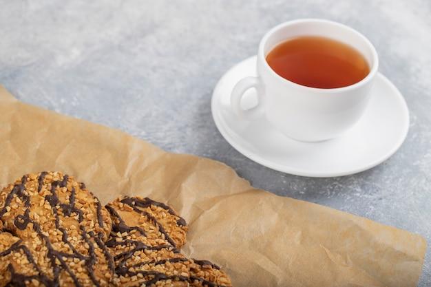 기름이 묻지 않는 종이에 초콜릿 코팅 된 오트밀 쿠키와 차 한잔.