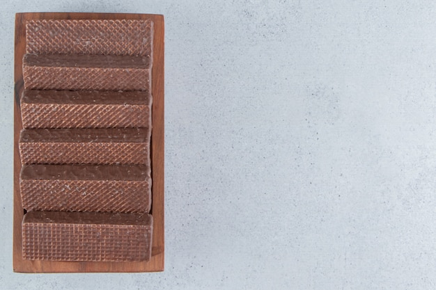 Вафли в шоколаде на деревянном блюде на мраморном фоне.