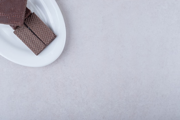 Chocolate coated wafers on a plate on marble table.