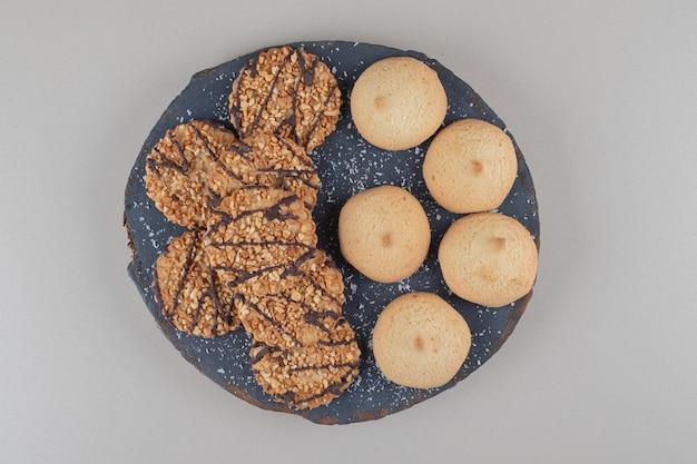 초콜릿 코팅 된 웨이퍼 대리석 배경에 검은 색 플래터에 쌓여있다.