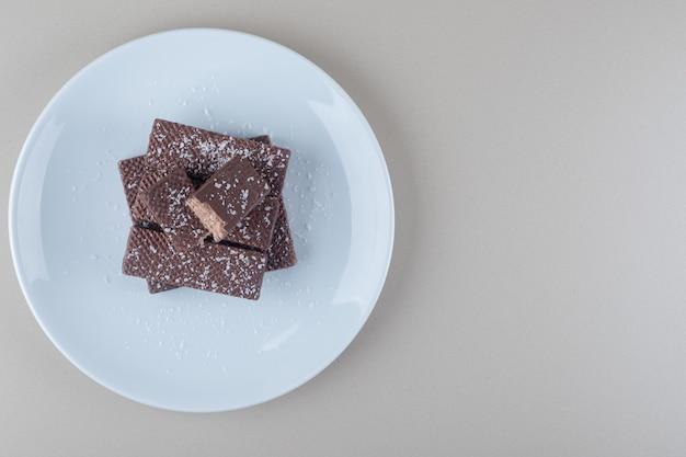 초콜릿 코팅 된 웨이퍼 대리석 배경에 흰색 플래터에 쌓여있다.