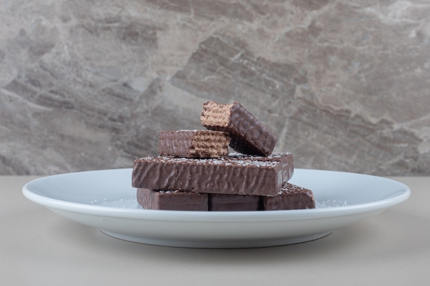 Chocolate coated wafers stacked on a white platter on marble background.