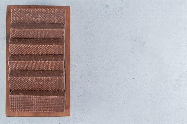 Wafer ricoperti di cioccolato su un piatto di legno su sfondo di marmo.