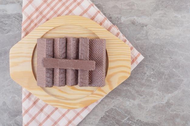Wafer ricoperti di cioccolato su un piatto di legno su marmo
