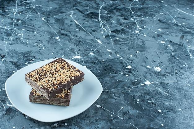 파란색 배경에 접시에 초콜릿 코팅 된 와플.