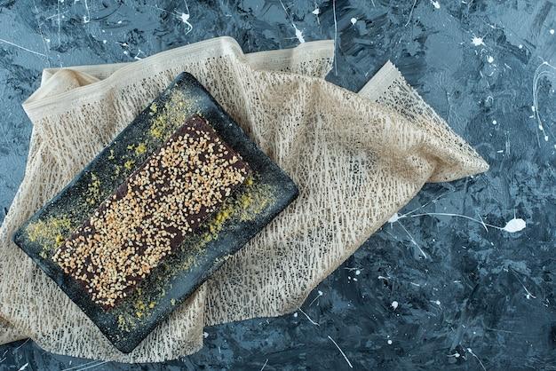 Cialda ricoperta di cioccolato su un piatto sulla tovaglia, sul tavolo blu.
