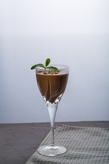 Chocolate cocktail with nuts and mint in a glass on a black background. vertical photo