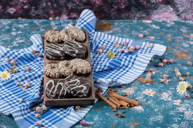 Biscotti al cioccolato e cocco su tavola di legno serviti con una tazza di tè.