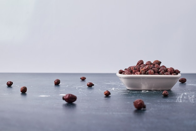 Chocolate coffee beans in a white ceramic plate.