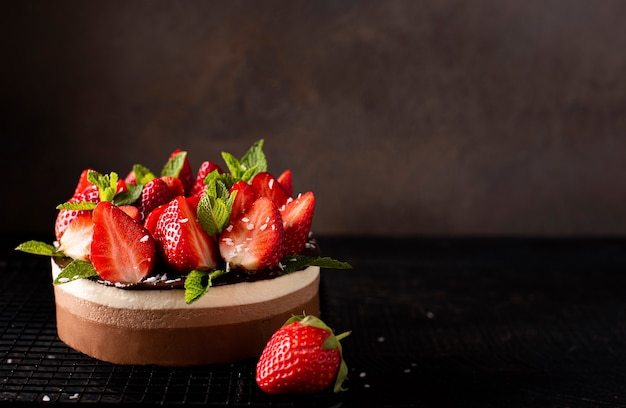Chocolate coffee cake with fresh strawberries and mint, copy space, close-up