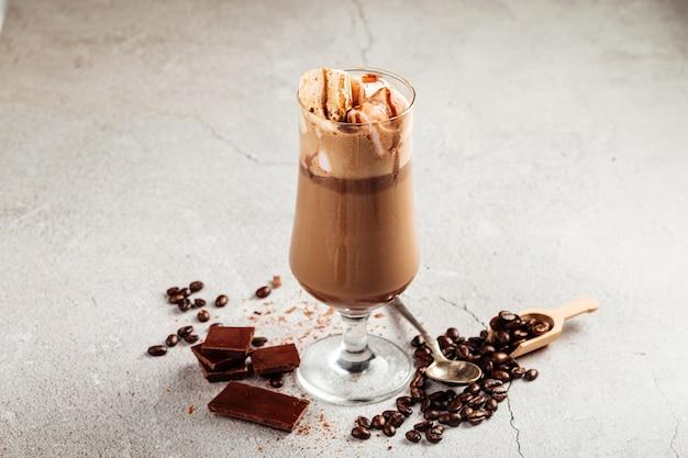 Шоколадно-кофейный стакан в стакане на бетонной поверхности, украшенный бобами и корицей