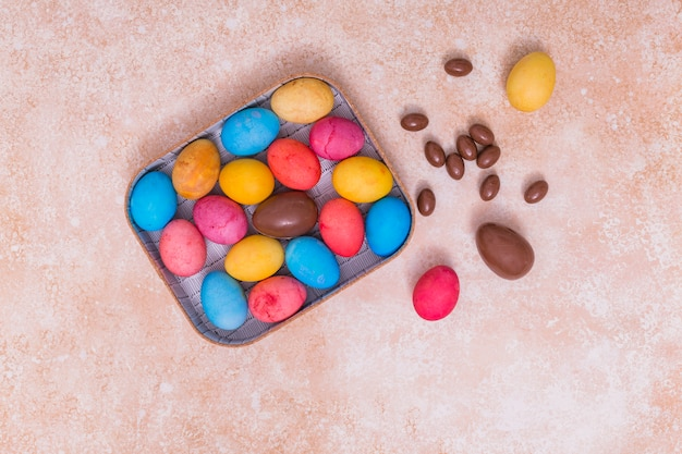 Chocolate and colorful easter eggs in box