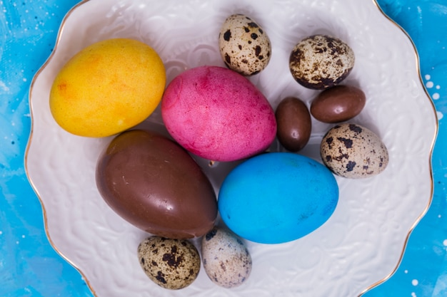 Chocolate and colorful easter eggs on plate