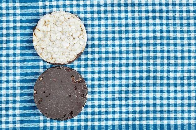 Un biscotto al cioccolato su una tovaglia blu.