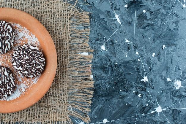 青いテーブルの上のテクスチャの粘土プレート上のチョコレートクッキー。