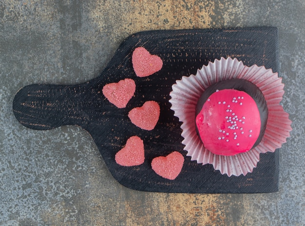 Chocolate cookie with pink glaze and candies on wooden board
