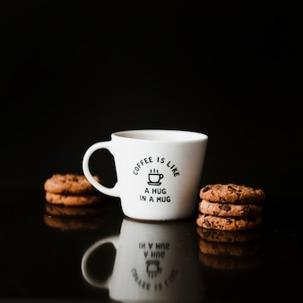 Chocolate cookies and ceramic cup on black background