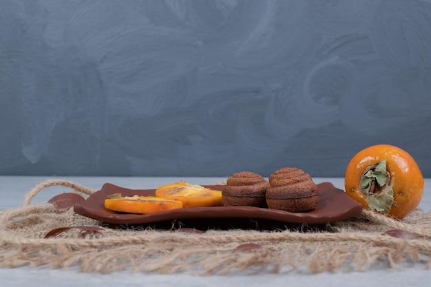 Шоколадное печенье и ломтики хурмы на тарелке. фото высокого качества