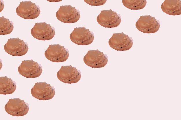 コピースペースのあるピンクの背景に斜めのパターンで配置されたチョコレートクッキー。甘い食べ物のクッキーのコンセプト。
