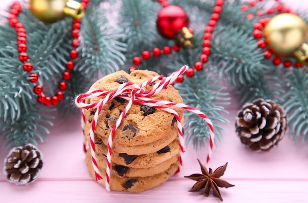 Chocolate cookies and christmas decoration on pink wooden