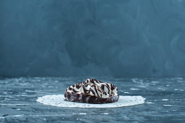 Biscotti al cioccolato su un sottobicchiere, sul tavolo blu.