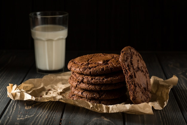 Chocolate cookies on craft paper with glass of milk