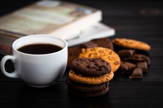 Chocolate cookies cup of coffee and book on wooden table. homemade food on wooden background.