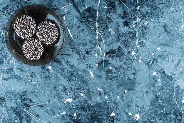 Biscotti al cioccolato su una lastra di vetro, sul tavolo blu.