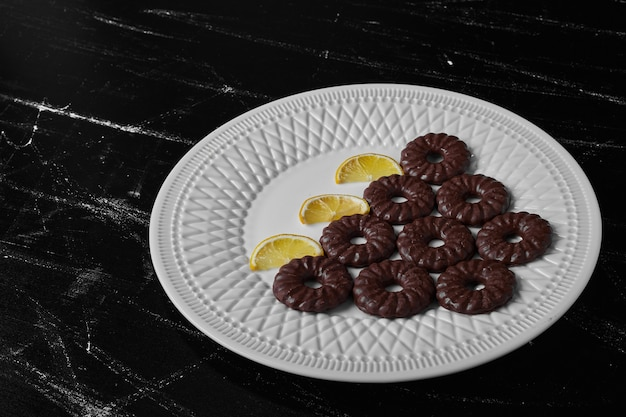 レモンと白いプレートのチョコレートクッキー。
