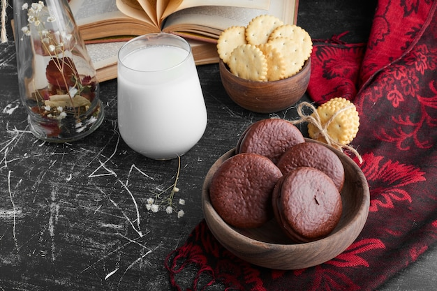 Шоколадное печенье в деревянной чашке со стаканом молока.