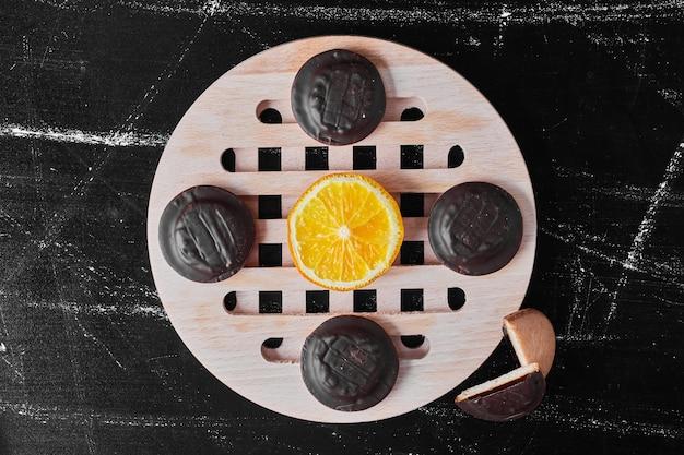 レモンと木製の大皿にチョコレートクッキー。