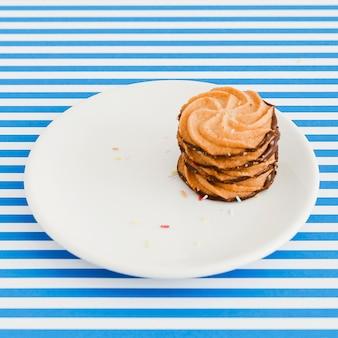 파란색과 흰색 줄무늬 배경 위에 접시에 초콜릿 쿠키