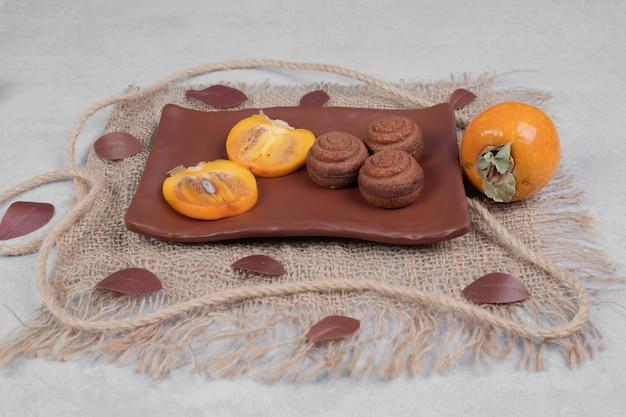 Biscotti al cioccolato e fette di cachi sulla piastra. foto di alta qualità